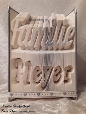 Ein Familienbuch mit dem eigenen Familiennamen, in einem gefalteten Buch.