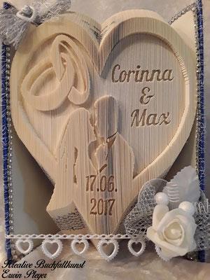 Ein gefaltetes Hochzeitsbuch in Form eines Herz, mit Ringen, einem Brautpaar, den Vornamen und dem Hochzeitsdatum.