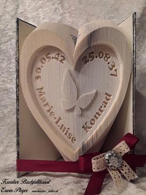 Ein Herz mit Namen und Geburtsdatum zum Jubiläum, 75er und 80er, in einem gefalteten Buch.