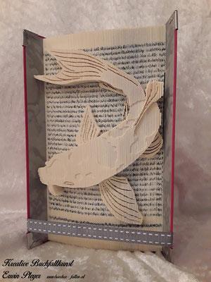 Dieser Koi scheint richtig aus dem gefalteten Buch heraus schwimmen zu wollen.