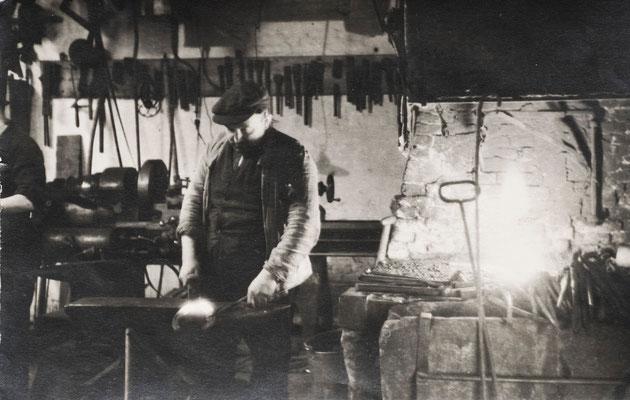 Smid Dirk Jan van Merkerk bezig met een hoefijzer - erachter het smidsvuur