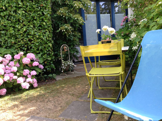 jardin privatif fleuri avec son salon de jardin et ses 2 transats