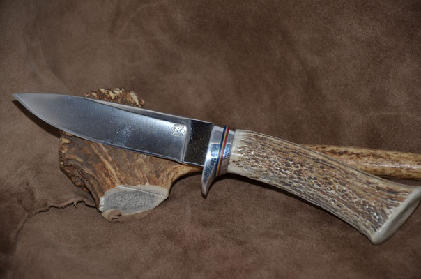 "#65 Drop Point.  Blade length 4 3/8"" Overall 9"" d2 steel.  Handle deer horn with red-white-blue spacers.  Aluminum guard.  Maker Steve Nolen  $250"