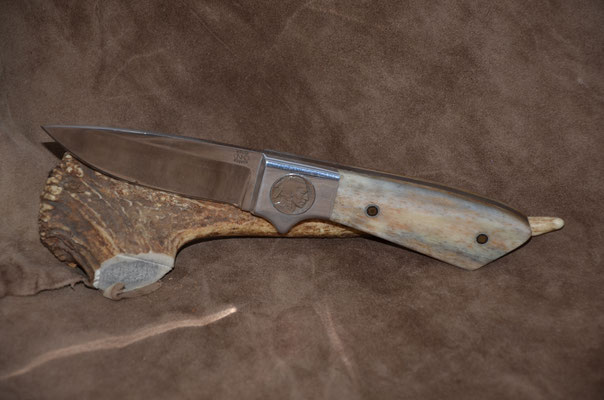 #148 Full tang drop point with bolsters that have buffalo nickles inlayed on one side and Indian head on other side.  Handle mammoth ivory.  Aluminum bolsters.  Maker RD Nolen  $400