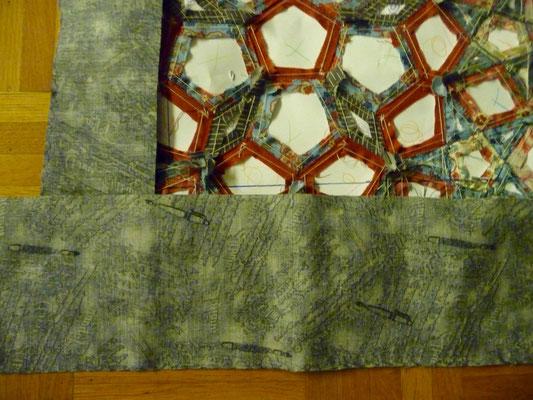 Den Randstoff (anthrazit) zunächst mit Pritstift/Klebestift  an der auf der Rückseite vom Quilttop aufgezeichneten Linie ankleben.
