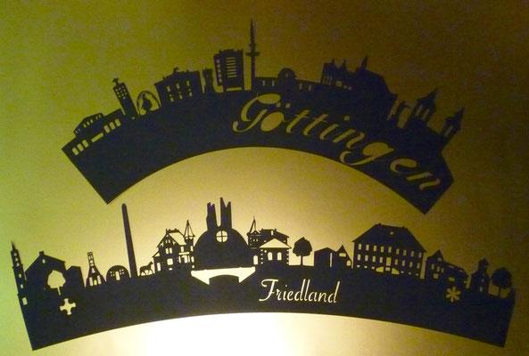 Die Skyline von Friedland und Göttingen als Scherenschnitt.