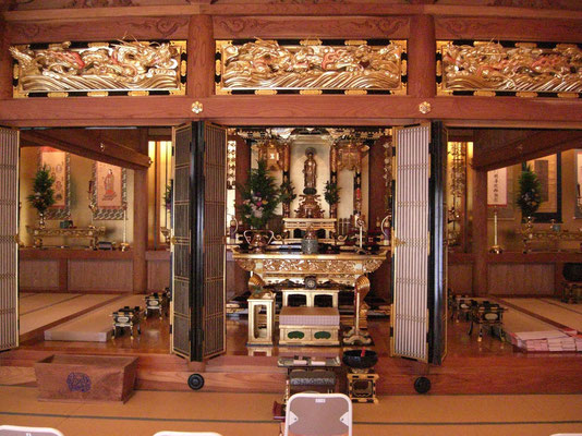 下陣側より内陣を見る: 真宗寺院では本堂は修行の場所ではなく聞法の道場と考えます。 そのため聞法の場所、下陣を広くしています。