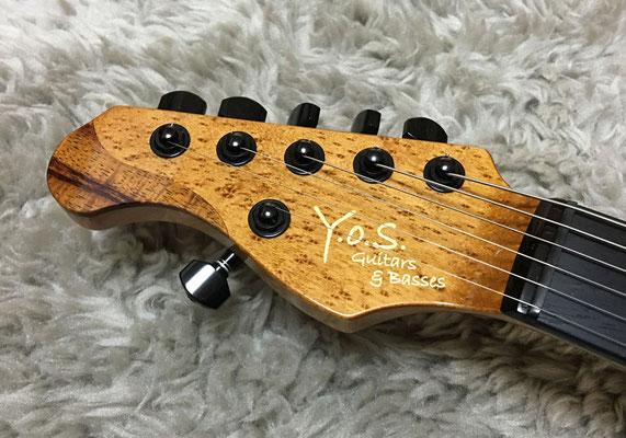 このギターの為にデザインされたペグ配置5:1のヘッド。ボディトップのコア材の余りをヘッド先端にインレイ加工している。メイプル部分はコアとの色味差を少なくするために染色。