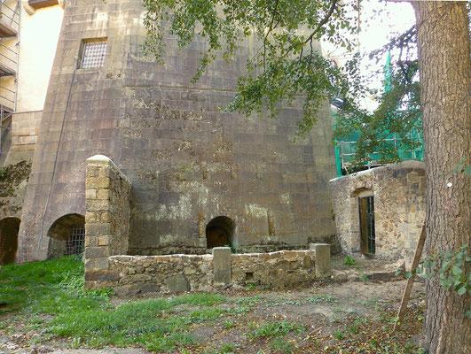 Die gewaltige nordwestliche Stützmauer der Hauptburg, direkt auf den Fels gesetzt.  Ansicht vom Schlossgarten aus. Rechts die Außenmauer des Gefängnishofes.