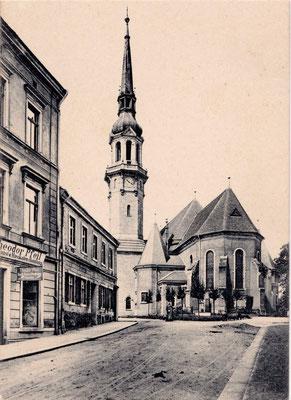 Links Kirchstraße 1, rechts im Erdgeschoss war die Buch-, Kunst- und Musikalienhandlung von Theodoer Pfeil eingemietet. Das anschließende Haus Kirchstr. 2 existiert nicht mehr.