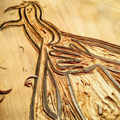 Detailansicht der in die Holzplatte geschnitzten Figur