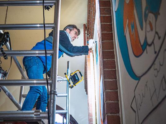 Frank Schulz auf einem Gerüst malt ein Acryl Wandgemälde