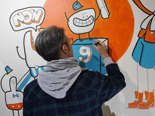 Der Künstler Frank Schulz zeichnet die Konturen seines Wandgemäldes.