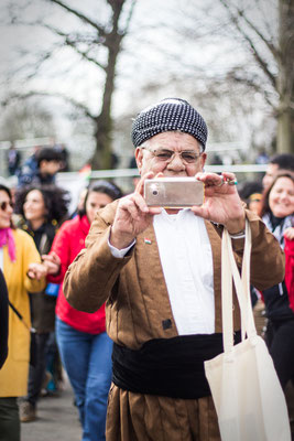 Kurdish man in traditional clothing, taking a picture with his phone of the Newroz festivities in London's Finsbury Park, March 2018.
