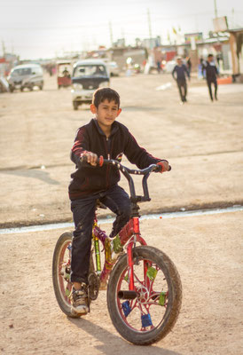 Syrian boy riding his bike in Domiz refugee camp in Kurdistan/Iraq. March 2017.