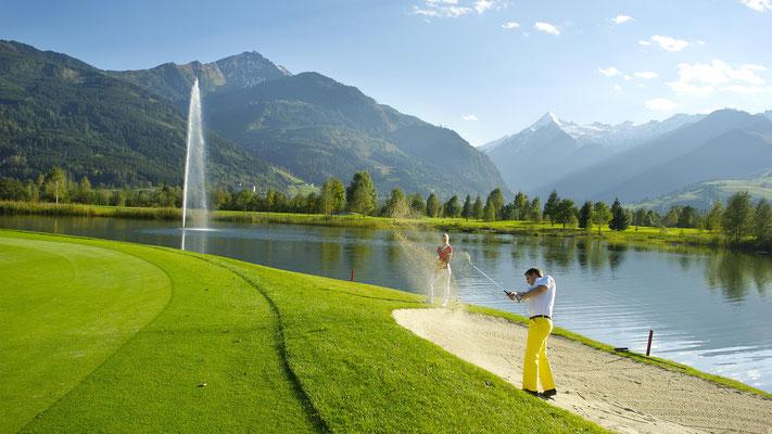 Abschlag am Golfplatz mit See