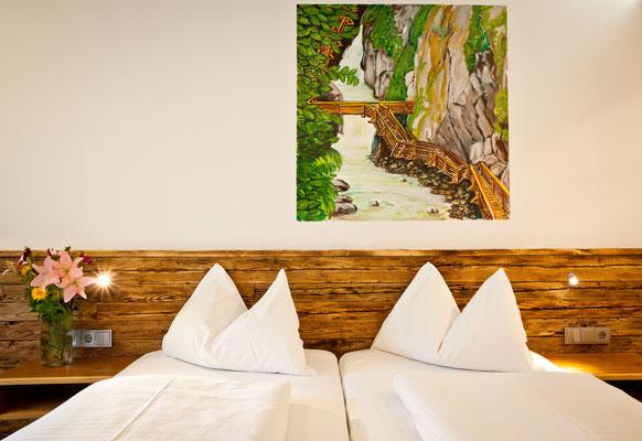 Gemachtes Bett mit Bild an Wand