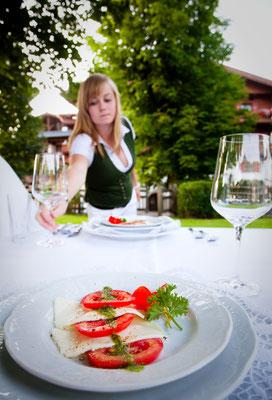 Frau im Dirndl am gedeckten Tisch