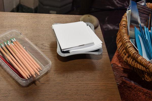 Neben Stiften und Notizzetteln liegen Karten und Blätter mit Worten der Hofnung bereit.