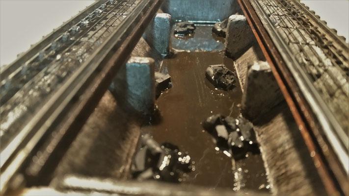 Installation des Rauchgenerators und erste Alterungsschicht mit erster Sumpfwasserschicht :) Die dicken schwarzen Körner sind Füllung für den später folgenden Aschehaufen und zugleich der Rand für die Dampfaustrittslöcher, damit das Wasser nicht durch fli