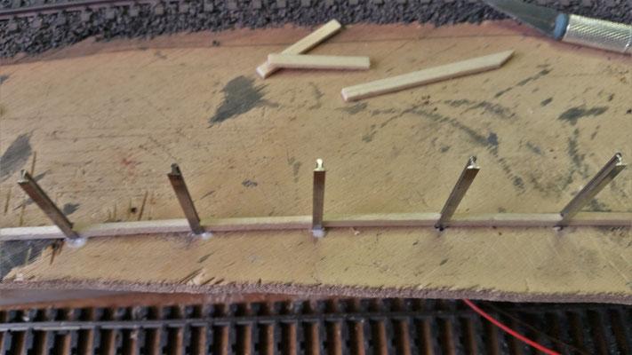 Die Träger werden in ein gebohrtes Loch gesteckt und in etwa gleichem Abstand geklebt. Dazwischen kommen die Bohlen
