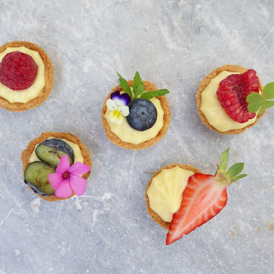 Mini tarts with a pastry cream filling and topped with fresh berries and flowers. Pasticcini.