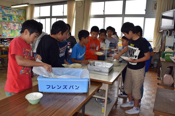 教室で給食を配膳する5年生