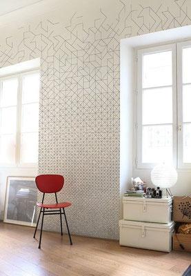 papier peint a motif géométrique et dégradé gris sur un mur proche de deux fenêtres