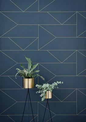 papier peint a motif géométrique bleu et doré avec des plantes placées devant