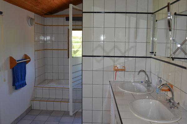 Badkamer met bad, aparte douche en dubbele wastafel.