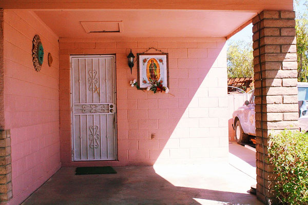 This house honors la Virgen with flowers and a beautiful tile piece. It also splashes its  neighborhood with a colorful bright pink.