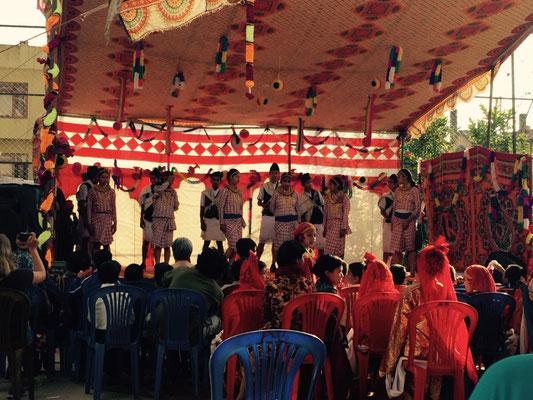 Das Programm ist klassisch nepalesisch, also sehr lang (drei bis vier Stunden), wenn von den Programmpunkten her recht abwechslungsreich. Nach Ellens Begrüßung folgen erst die Nationalhymne und anschließend ein paar traditionalle Tänze.