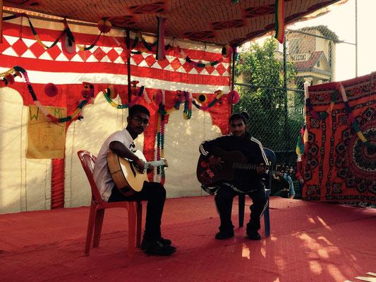 Sachin und Ramesh spielen Gitarre.