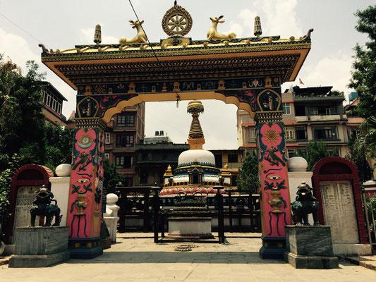 Ein ganz typisch nepalesisches farbenfrohes Tor vor einem Stupa