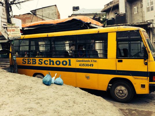Der Schulbus steht abfahrtbereit am Fuße des Hügels.