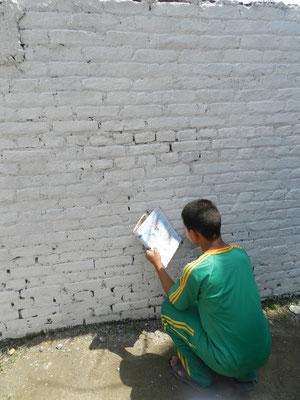 Nun zeichnet Kamal mit dem Bleistift eine Weltkarte auf die rechte Seite der Mauer.