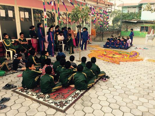 Das erste Haus, wo gesungen wird, ist das eigene. Also setzen sich alle Kinder auf Teppiche und lauschen dem Gesang.