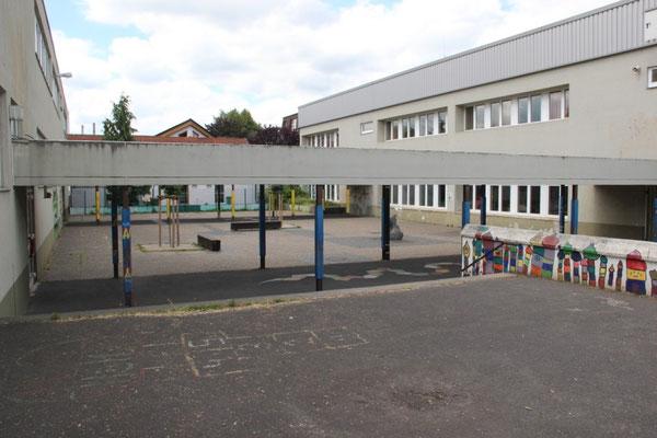 Kleiner Innenhof zwischen den Klassenzimmern:  Zwei kleine Bäume, zwei Bänke und ein aus Sicherheitsgründen halb demontierter Springbrunnen dominieren das triste Bild zwischen den 40 Jahre alten grauen Unterrichtsgebäuden.