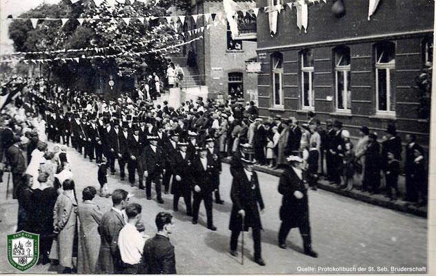 Festzug über die Bahnstraße 1934. Bildmitte: Aufgang zur Kath. Pfarrkirche und Wegkreuz. Quelle: Protokollbuch der SSB