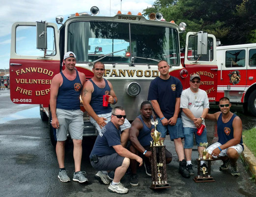 "Posing in front of the now-retired Engine 7 with the ""Tug 'O War"" and ""Best Looking Crew"" awards - (l-r) FF Fourre, FF Grasso, Asst Chief Zawodniak, FF Green, FF Weisglass, FF Padulsky, Captain Piccola"
