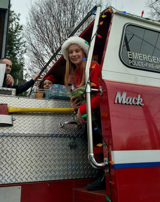 Firefighter Jimmy Drewes, Melissa Drewes, and one of Santa's helpers