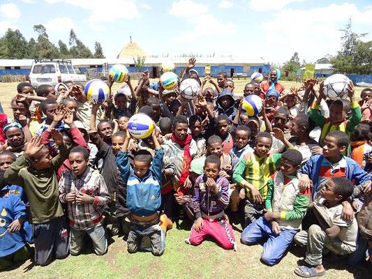 Kinder freuen sich über Volleybälle und Fußbälle