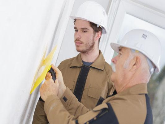 Ein Mitarbeiter der 3B Denkmalpflege & Bausanierung GmbH zeigt einem Azubi die richtige verputz Methode