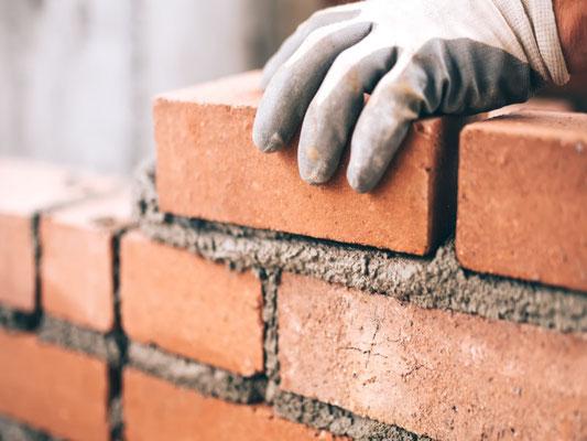 Ein Maurer der 3B Denkmalpflege & Bausanierung GmbH beim setzten von Steinen