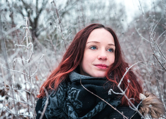 Bild einer rothaarigen Frau auf einer verschneiten Wiese