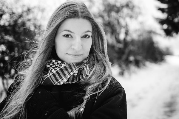 Die Haare einer Frau wehen im Wind auf einen schneebedeckten Weg bei Bamberg