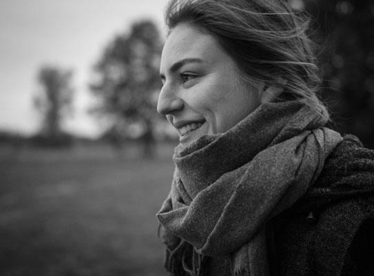 Lachende Frau mit Schal vor Bäumen in Erlangen