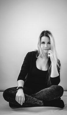 Portrait einer Frau im Schneidersitz