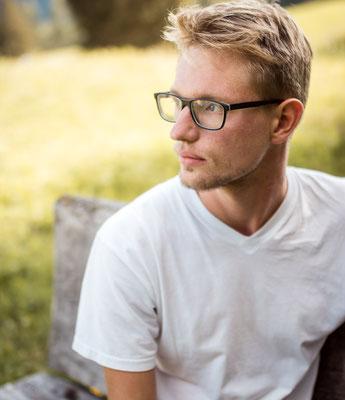 Mann mit Brille auf einer Bank