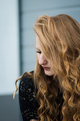 Melancholische Frau versteckt sich unter ihren lockigen blonden Haaren